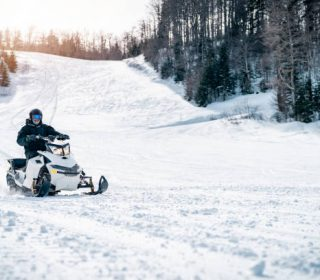 Young man driving a snowmobile