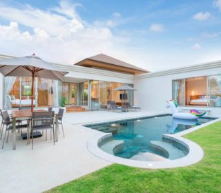 home or house  Exterior design showing tropical pool villa with greenery garden, sun bed, umbrella, pool towels and colorful floating unicorn