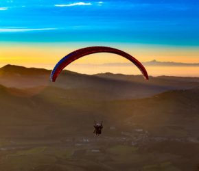 a tandem flight  paraglider flying  over a valley with alps range at the horizon