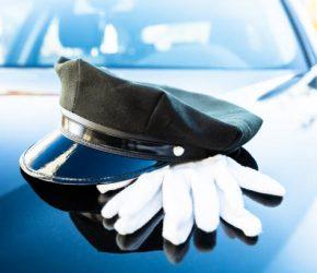Black Chauffeur's Cap And Pair Of White Hand Gloves On Car Bonnet