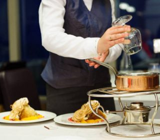 A waitress at table side elegantly pouring in the liquor to make the flaming Crepes Suzette in a luxurious hotel / restaurant in Deauville, France.