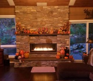 Beautiful stone mason fireplace, flames glowing at dusk, in a large rustic home-like setting, during the autumn/fall holiday timeframe. Cozy, grand, special.