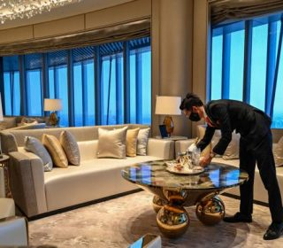 An employee is seen in a suite room of the J Hotel, the world's highest luxury hotel, boasting a restaurant on the 120th floor and 24-hour personal butler service, located in the Shanghai Tower, in Shanghai on June 23, 2021. (Photo by Hector RETAMAL / AFP) (Photo by HECTOR RETAMAL/AFP via Getty Images)