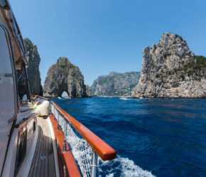 View of the amazing island of Capri and the Faraglioni from a boat,  Campania, Italy.