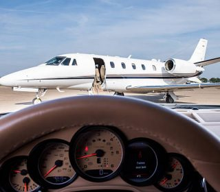 Private jet airplane on the airport track viewed from the seat of a car driver. Gauges and steering wheel are seen in front.