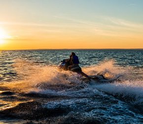 People having fun riding a person watercraft/water scooter on the sea in the sunset.