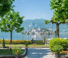 Orta with lake and island San Giulio in a sunny day with mountain and trees in Piedmont, Italy.