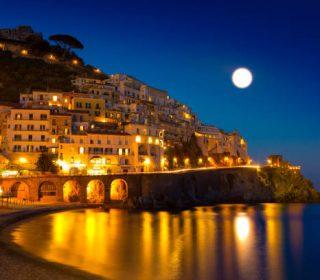 Night view of Amalfi cityscape on coast line of mediterranean sea, Italy