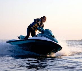 beautiful girl riding her jet skis in the sea at sunset. spray